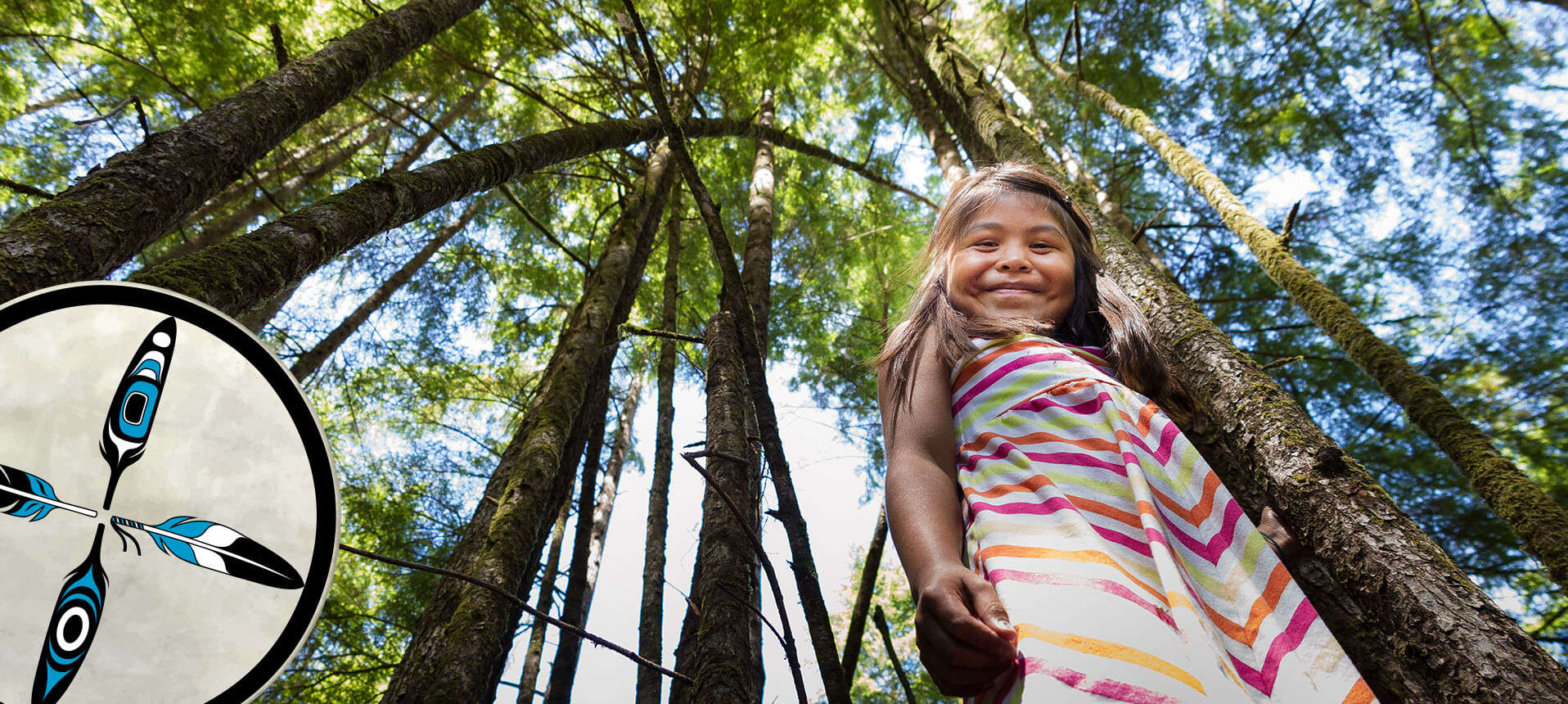young girl smiling down at camera standing in the forest